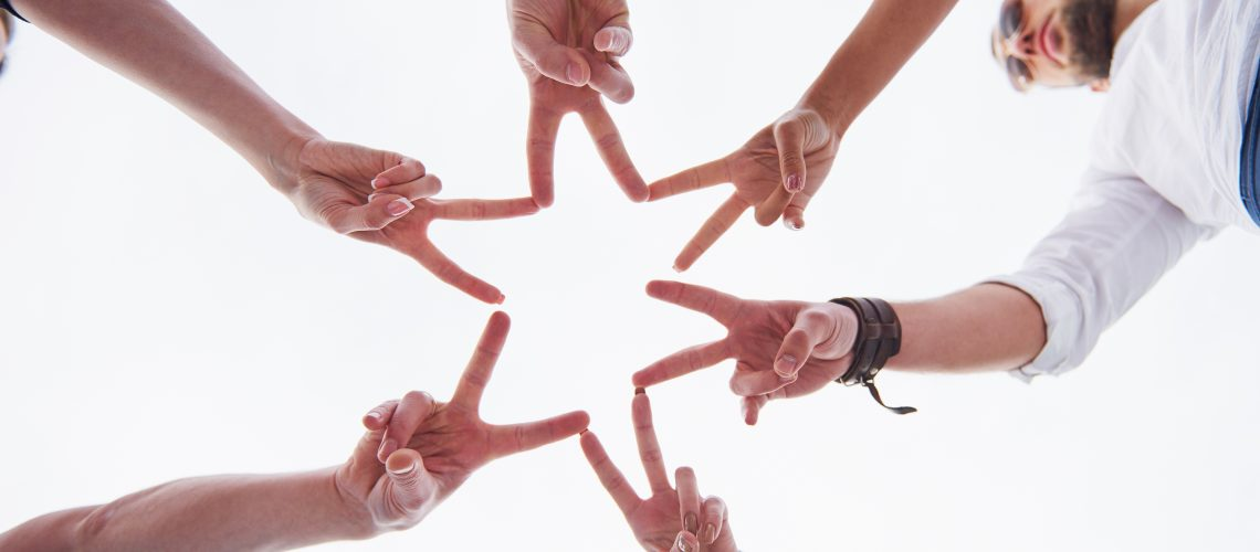 People forming star shape with their fingers.